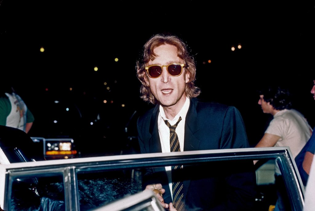 """John Lennon near a car years after working on a famous cover of The Beatles' """"Lucy in the Sky with Diamonds"""""""