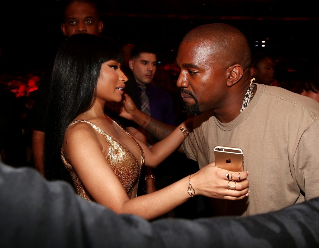 Nicki Minaj putting her arm around Kanye West