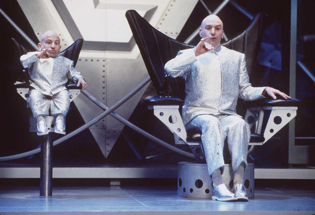 Mini-Me and Dr. Evil sitting in chairs