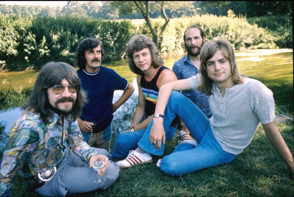 The Moody Blues sitting on the grass