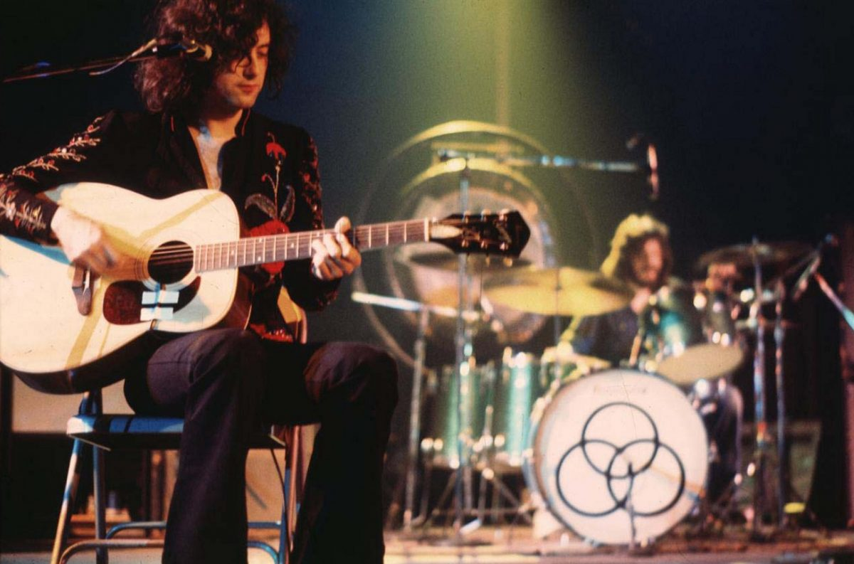 Page seated with guitar and Bonham at the drums on stage