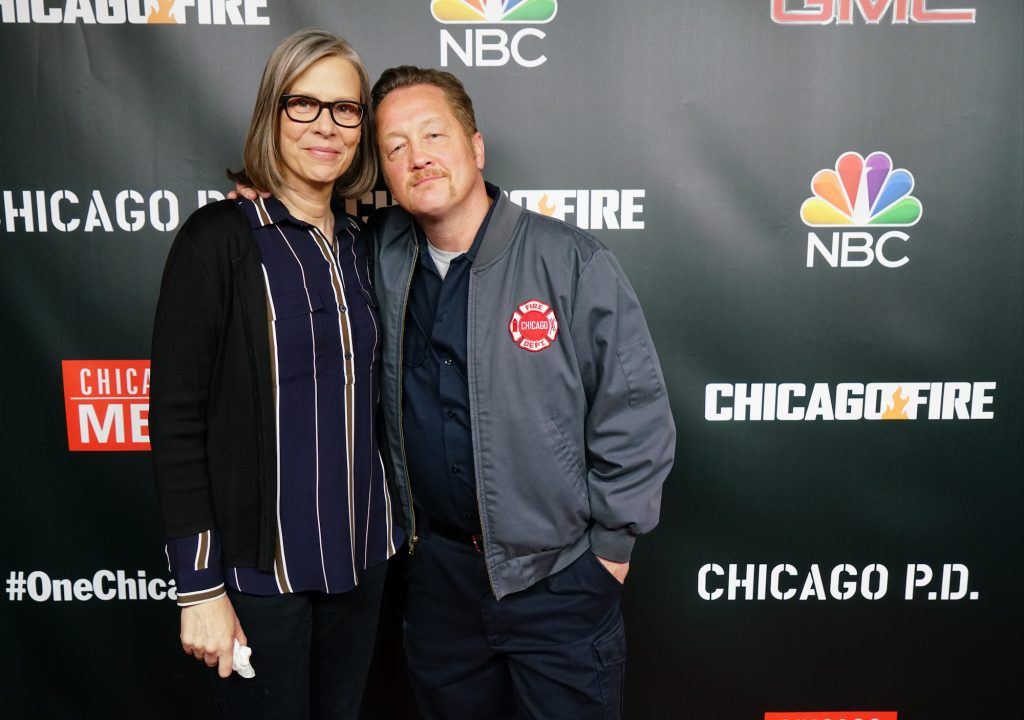 Amy Morton and Christian Stolte, embracing, smiling in front of a black background