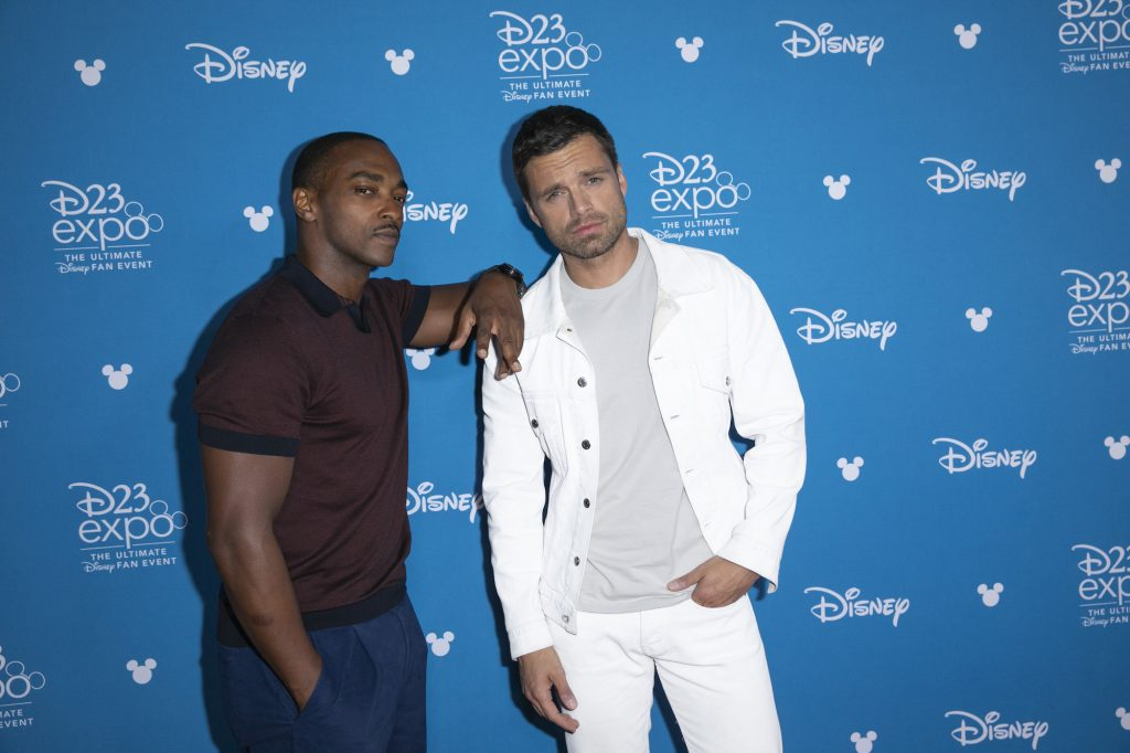 Anthony Mackie leaning on Sebastian Stan, looking at the camera in front of a blue background