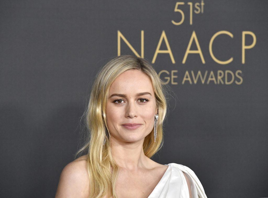 Brie Larson smiling in front of a dark background