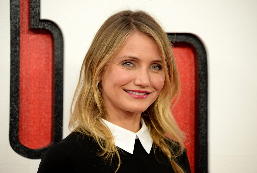 Cameron Diaz smiling in front of a white, red, and black background