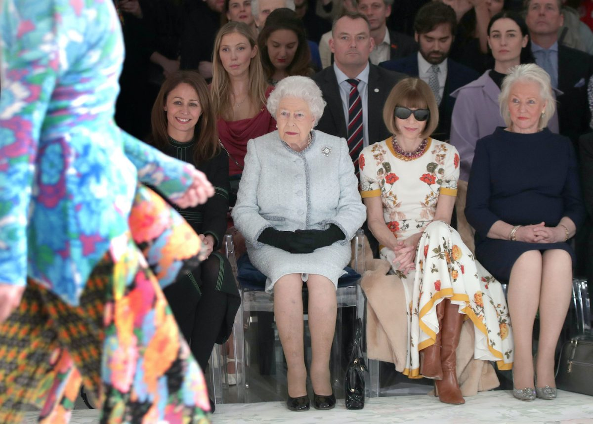 Caroline Rush, Queen Elizabeth II, Anna Wintour, and Angela Kelly sit in the front row of a fashion show