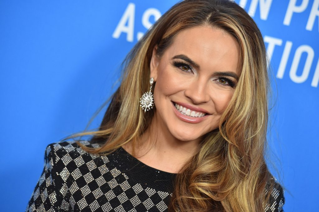 Chrishell Stause smiling in front of a blue background