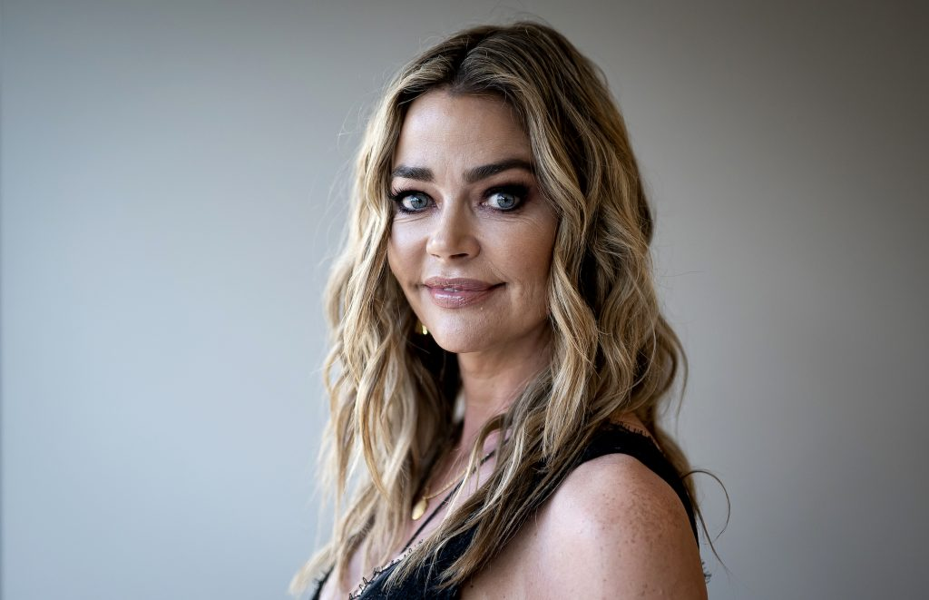 Denise Richards smiling at the camera, turned to the side