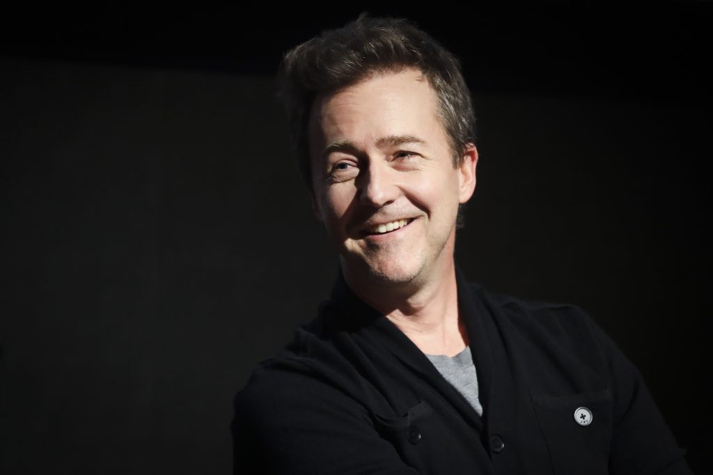 Edward Norton laughing, looking off camera, in front of a black background