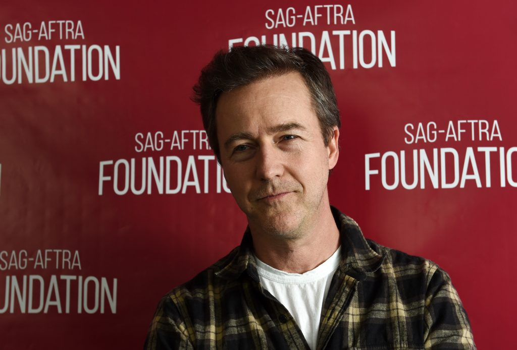 Edward Norton slightly smiling in front of a red background