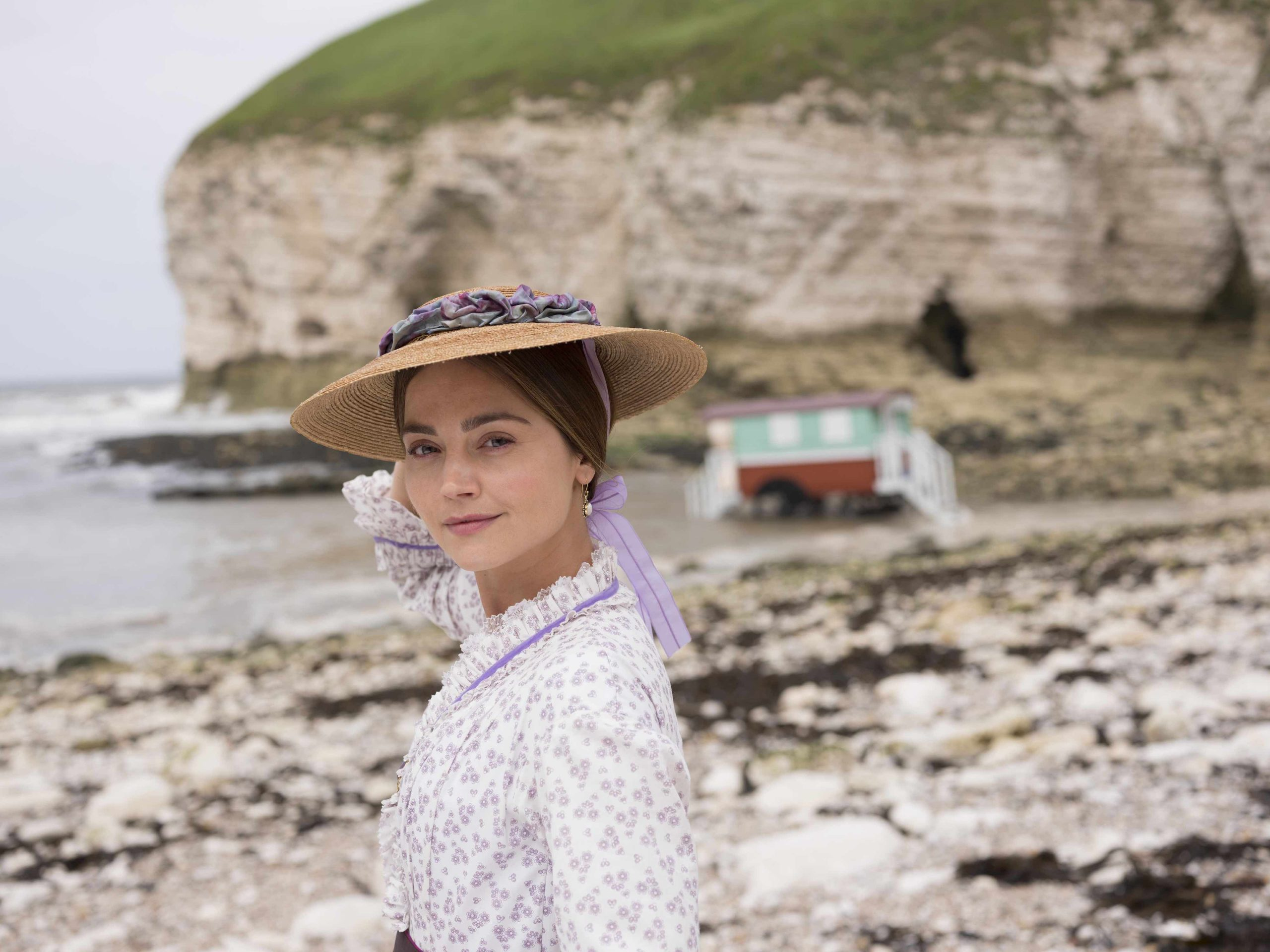 Jenna Coleman as Queen Victoria wearing a straw hat and standing on a beach