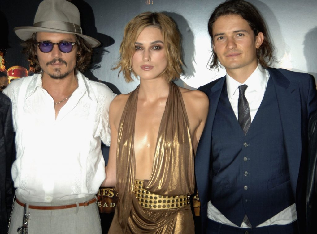 Johnny Depp, Keira Knightley, and Orlando Bloom smiling at the camera