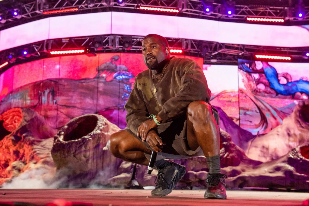Kanye West crouched on stage, looking off camera