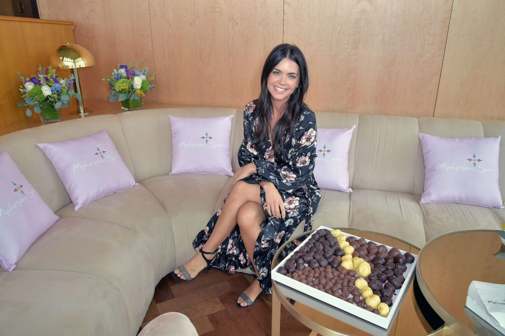 Katie Lee sitting on a couch, smiling