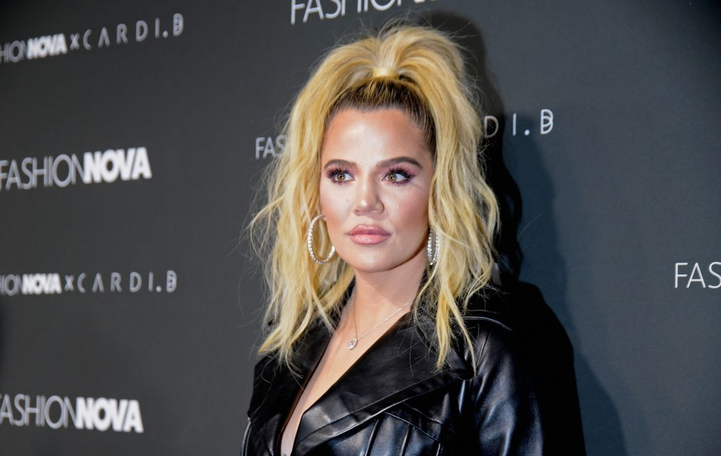 Khloé Kardashian posing in front of a black background