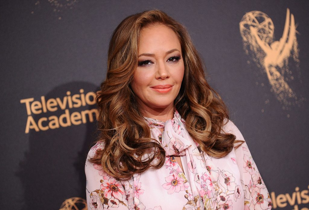 Leah Remini smiling in front of a dark background