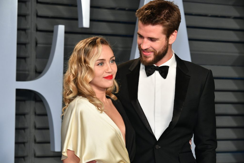Miley Cyrus (L) and Liam Hemsworth attend the 2018 Vanity Fair Oscar Party hosted by Radhika Jones at Wallis Annenberg Center for the Performing Arts on March 4, 2018 in Beverly Hills, California