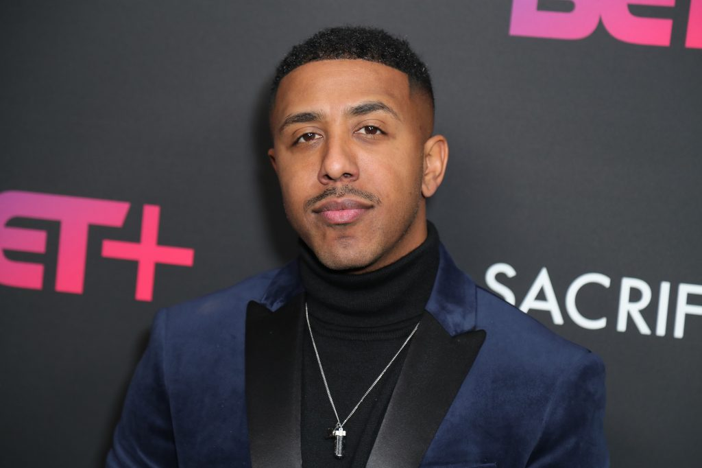 Marques Houston smiling in front of a black wall