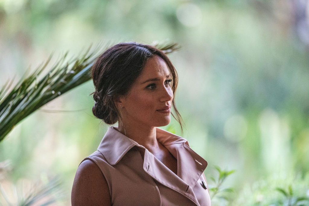 Meghan Markle looking off to the side in front of a blurred green background
