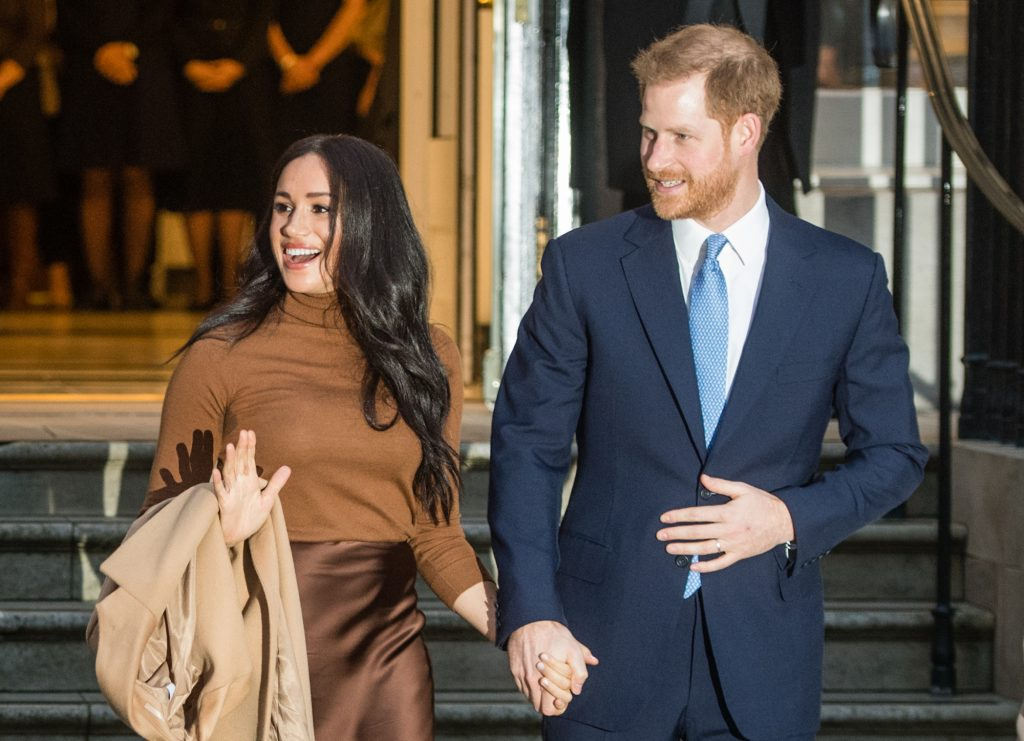 Meghan Markle and Prince Harry, smiling, turned to the side