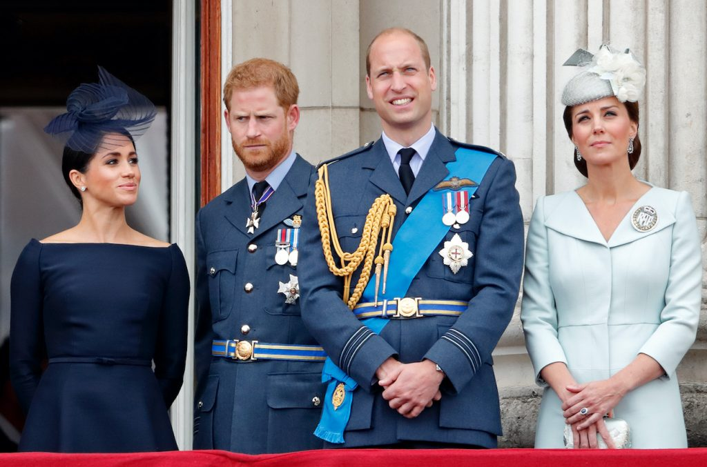 Meghan Markle, Prince Harry, Prince William, and Kate Middleton stand on the balcony of Buckingham Palace attending the centenary of Royal Air Force