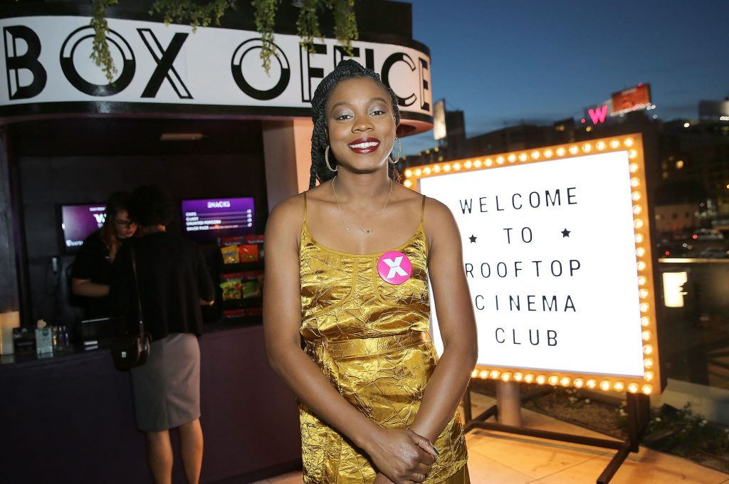Nia DaCosta smiling in front of a light up sign