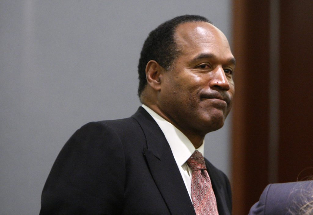 O.J. Simpson looking away from the camera in front of a gray wall
