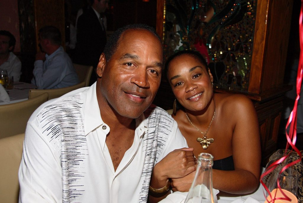 (L-R) O.J. Simpson and Arnelle Simpson smiling at a dinner table