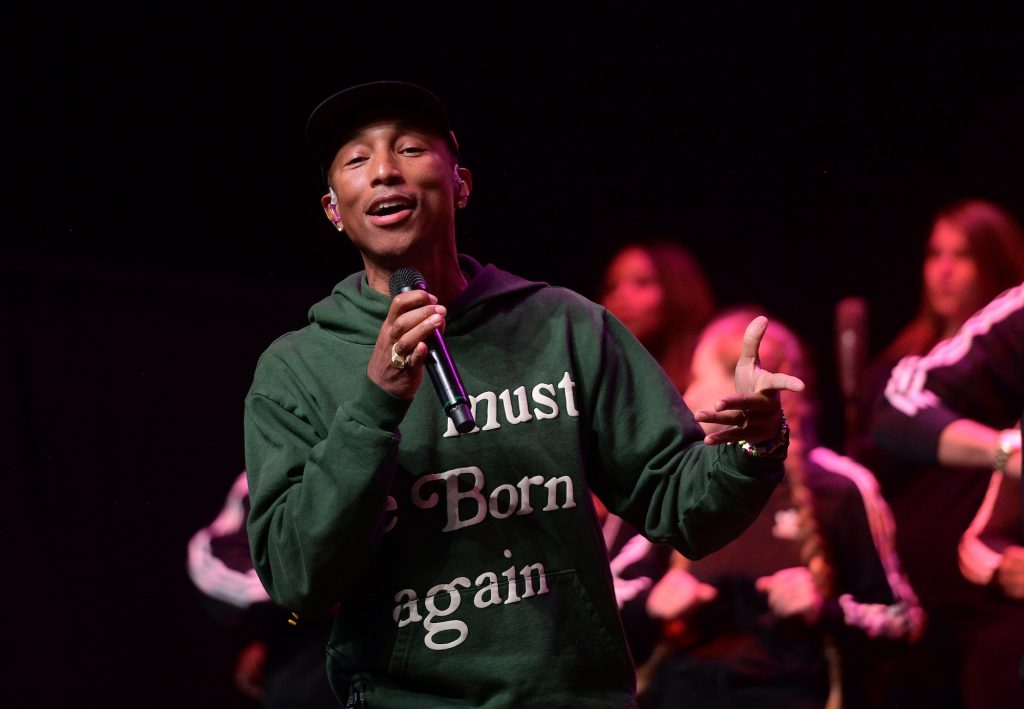 Pharrell Williams smiling on stage, holding a microphone