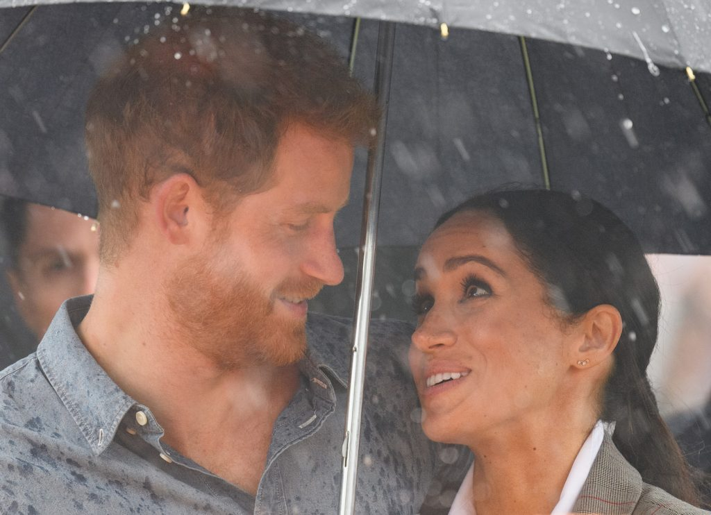 Prince Harry and Meghan Markle stand under an umbrella during a visit to Dubbo, Australia