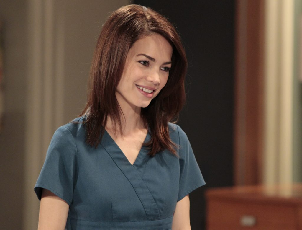 Rebecca Herbst smiling, looking away from Fahad Tamimi the camera