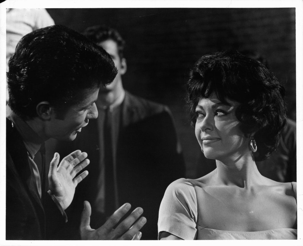 Rita Moreno listens while George Chakiris speaks with her in a scene from 'West Side Story' (1961)