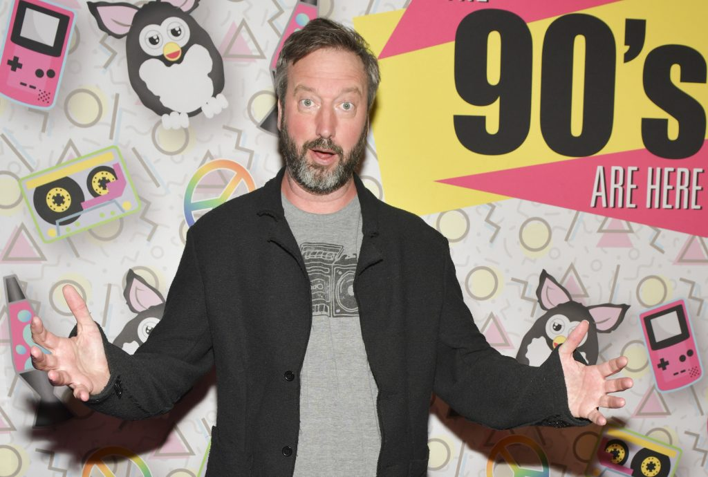 Tom Green with his arms out in front of a patterned background
