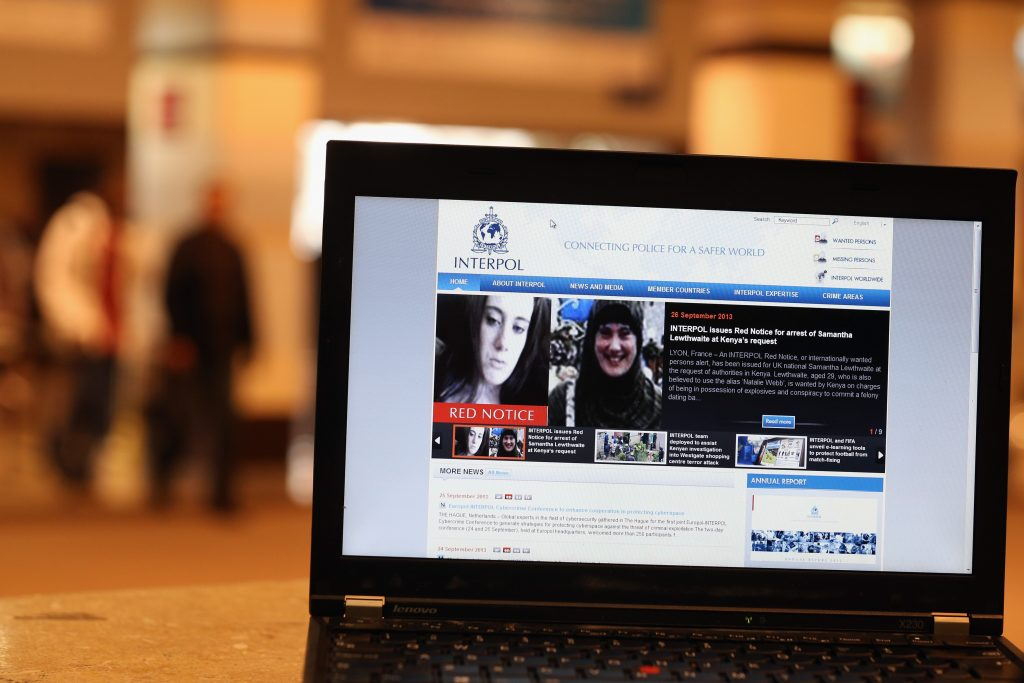 A view of a laptop computer screen showing the Interpol website which features a 'Red Notice' for the arrest of Samantha Lewthwaite