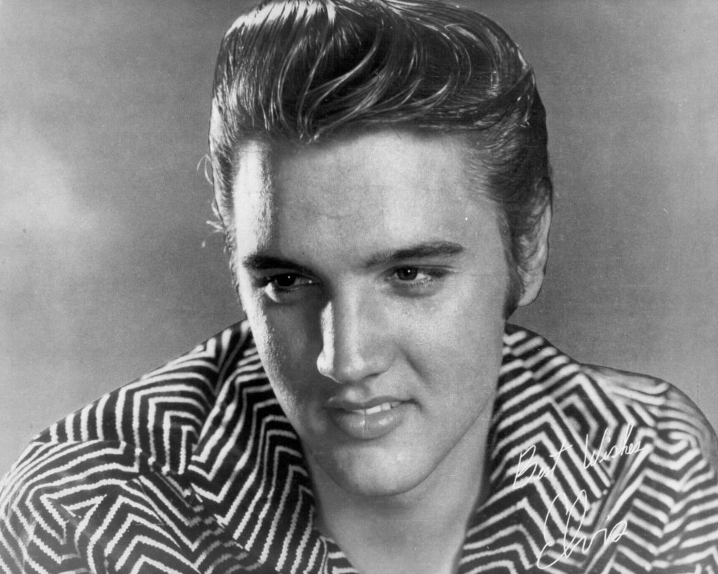 Elvis Presley smiling and wearing a striped shirt in a photo with his signature