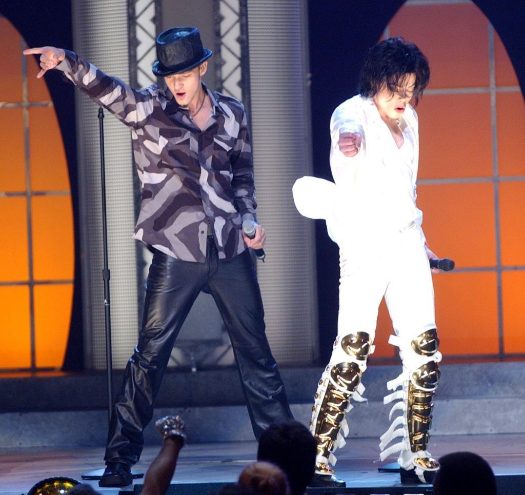 Justin Timberlake and Michael Jackson raising their arms