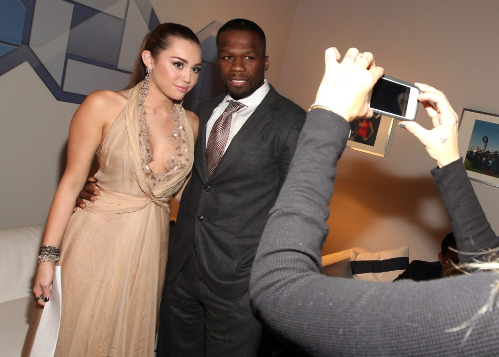 Someone taking a picture of Miley Cyrus and 50 Cent on their phone