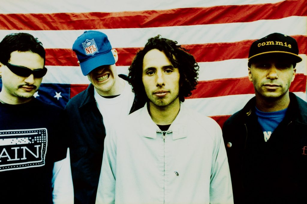 Rage Against the Machine posed in front of upside-down American flag