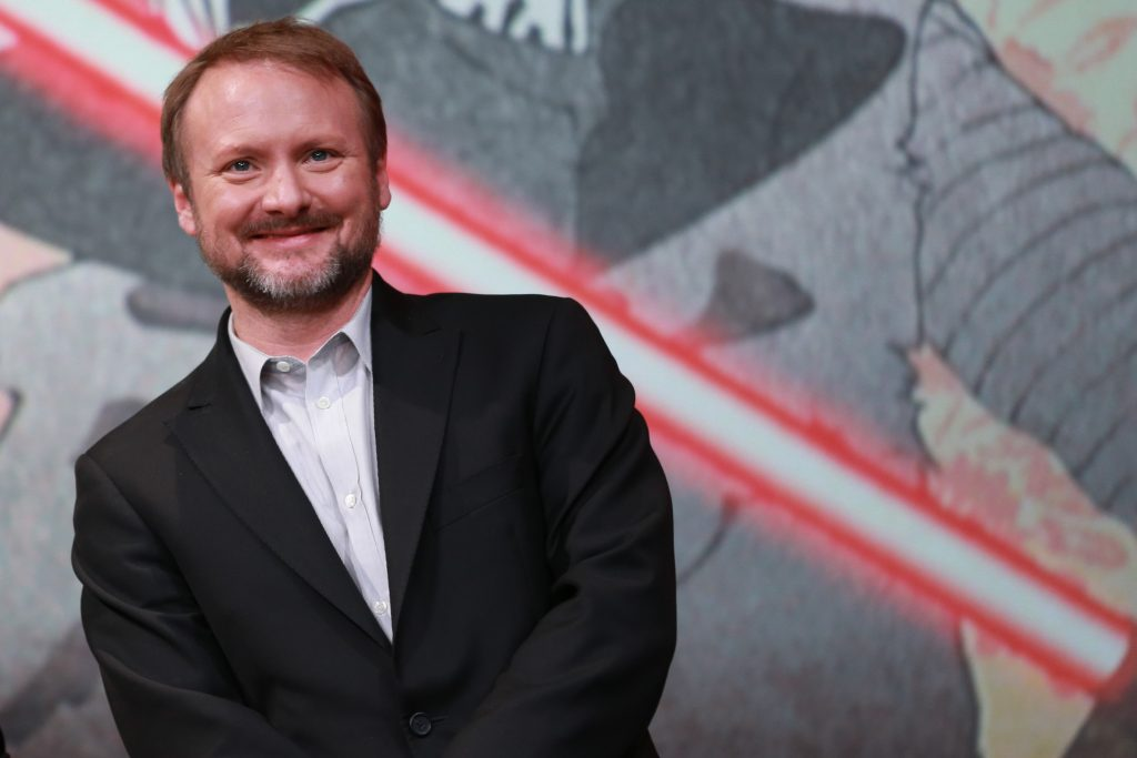 Rian Johnson in front of a Star Wars poster