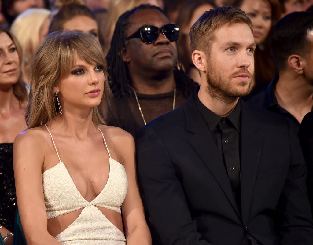 Taylor Swift and Calvin Harris seated in a crowd