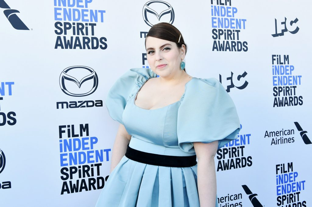 Beanie Feldstein smiling in front of a white and blue background