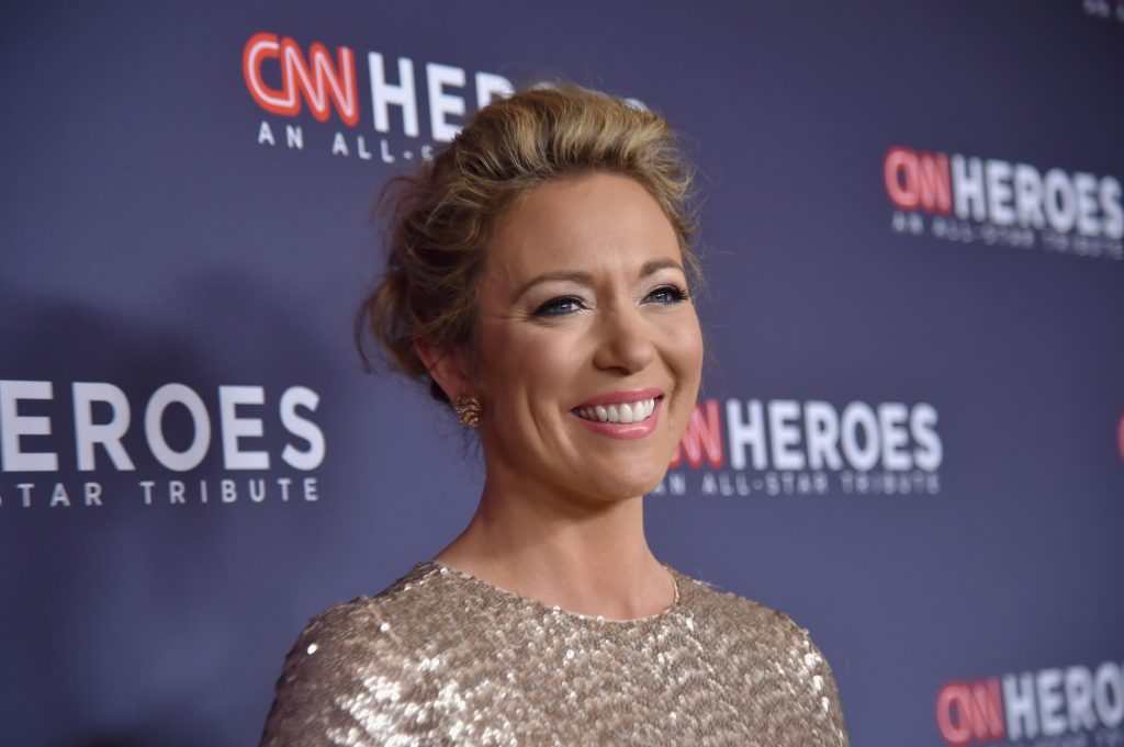 Brooke Baldwin smiling in front of a blue background