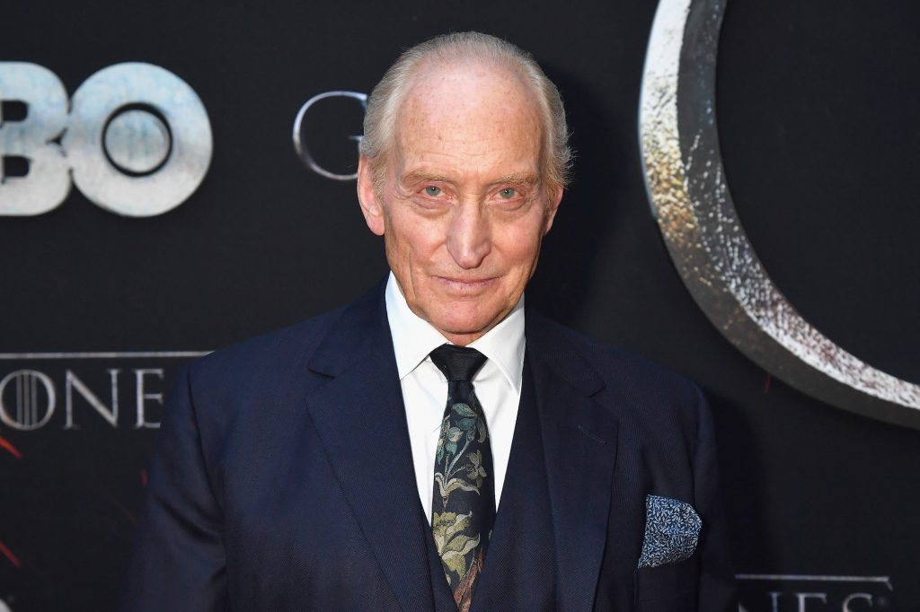 Charles Dance smiling in front of a black background