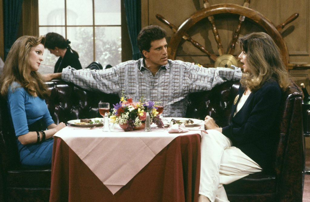 (L-R) Marcia Cross as Susan Howe, Ted Danson as Sam Malone, Kirstie Alley as Rebecca Howe at a table in front of a large ship wheel