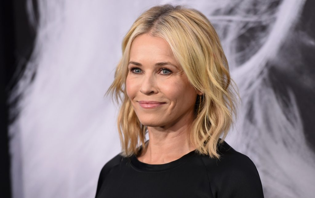 Chelsea Handler smiling in front of a blurred background