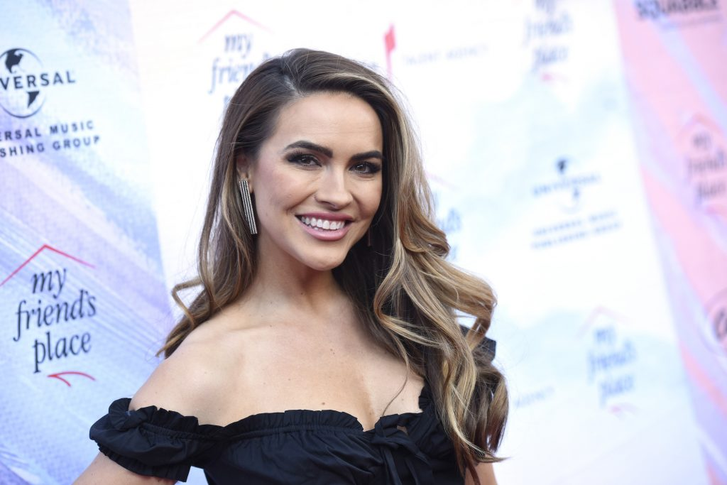Chrishell Stause smiling in front of a light colored background