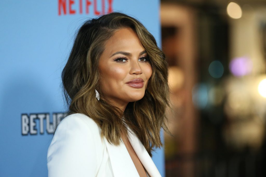 Chrissy Teigen smiling in front of a blurred background