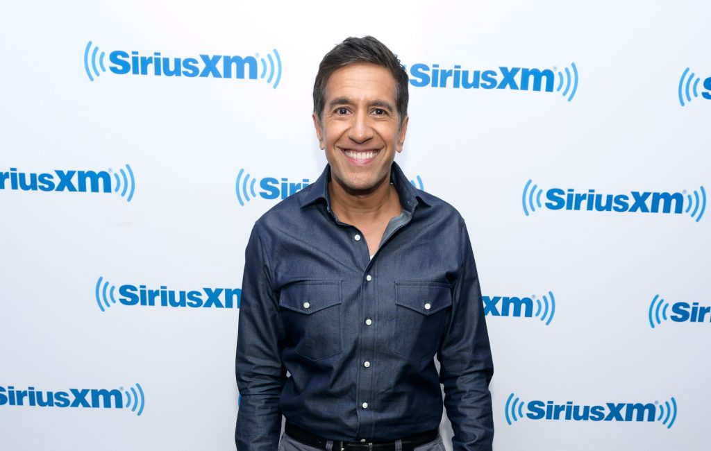 Dr. Sanjay Gupta smiling in front of a white background