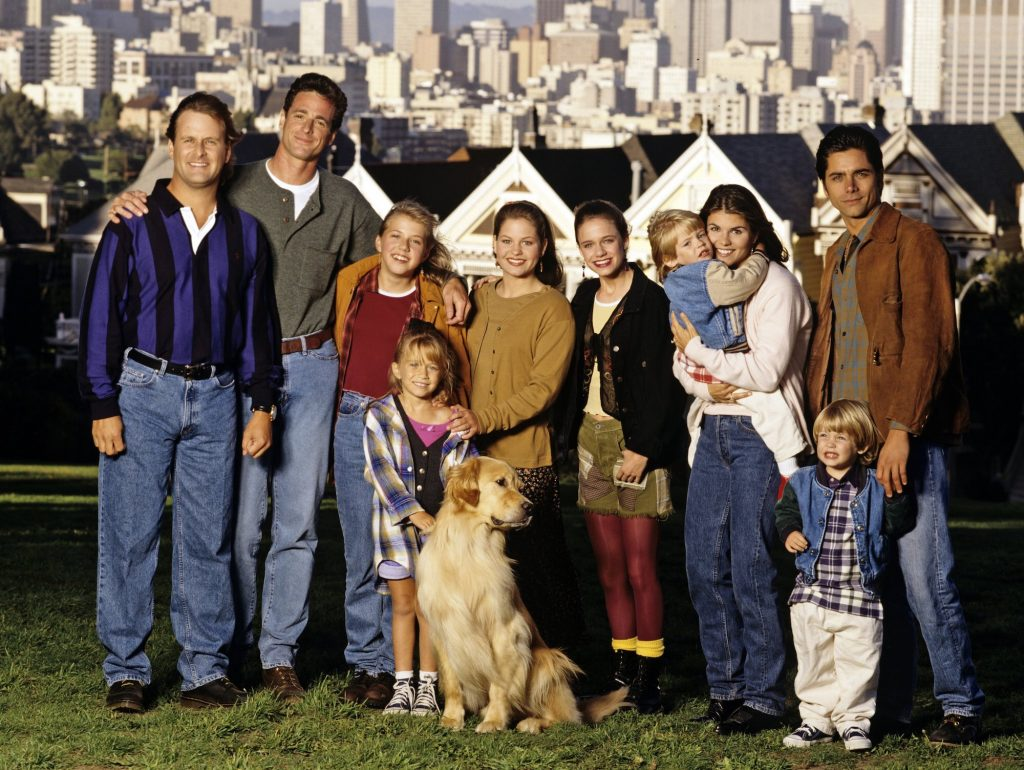 (L-R) Dave Coulier (Joey), Bob Saget (Danny), Jodie Sweetin (Stephanie), Mary Kate Olsen (Michelle), Candace Cameron (D.J.), Andrea Barber (Kimmy), Blake Tuomy-Wilhoit (Nicky), Lori Loughlin (Rebecca), Dylan Tuomy-Wilhoit (Alex), John Stamos (Jesse) smiling in front of the famed 'Full House' houses