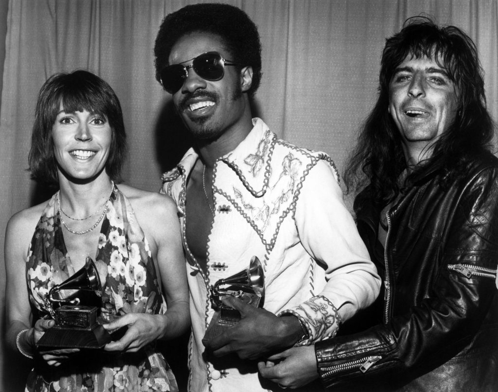 Helen Reddy in 1973 with her Grammy Award for her song 'I Am Woman'. She is pictured with Stevie Wonder and Alice Cooper.